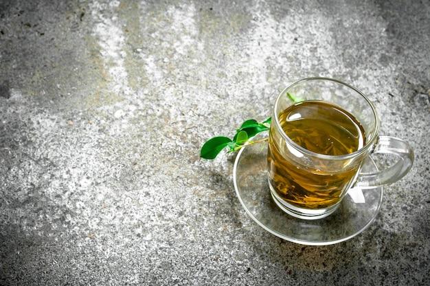 Thé vert dans une tasse en verre sur un fond rustique