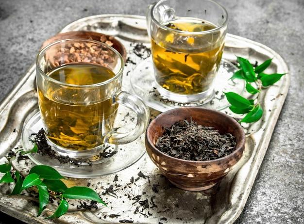 Thé vert frais sur un plateau en acier sur un fond rustique