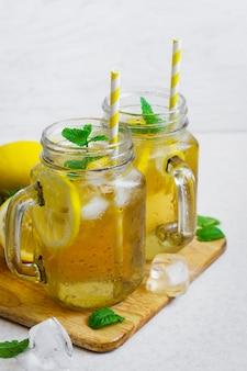 Thé vert glacé au citron et à la menthe dans un bocal en verre.