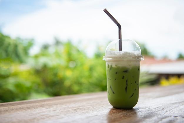 Thé vert glacé dans une tasse en plastique / thé vert matcha frappé au latte et paille sur une table en bois avec la nature