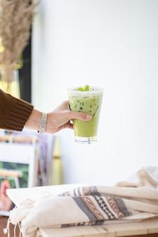 Thé vert glacé ou matcha latte sur de grands verres avec de la paille sur un objet de décoration de table et de vêtements en bois blanc.