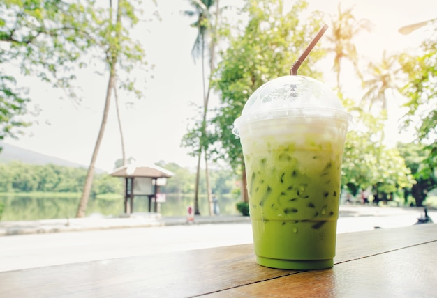 Thé vert glacé sur une table en été avec le fond naturel.