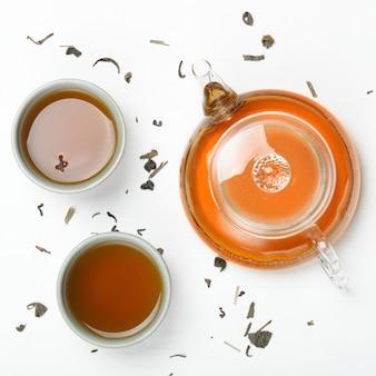 Thé vert infusé dans une théière transparente et dans de petites tasses sur une table blanche avec du thé dispersé. cérémonie du thé concept, traditions chinoises. vue de dessus, pose à plat