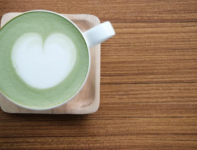 Thé vert matcha avec art au coeur sur table en bois