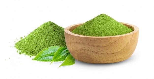 Thé vert matcha dans un bol en bois avec des feuilles sur blanc
