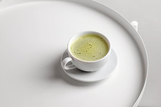 Thé vert matcha avec du lait dans une tasse sur tableau blanc et fond blanc