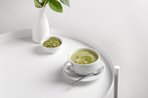 Thé vert matcha avec du lait dans une tasse sur un tableau blanc et un fond blanc
