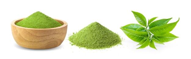 Thé vert matcha instantané dans un bol en bois et feuilles sur fond blanc