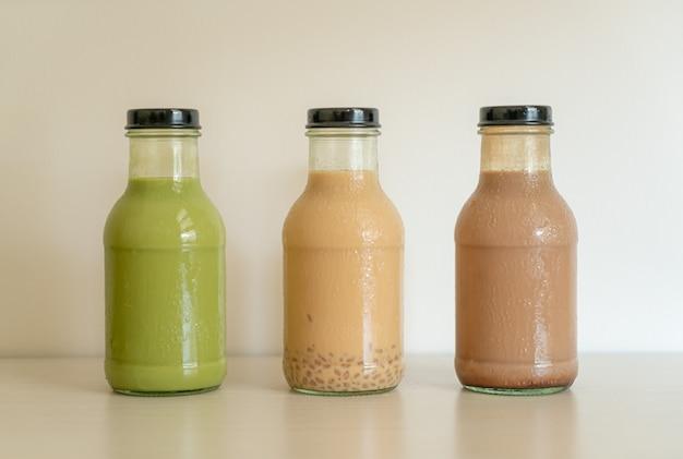 Thé vert matcha latte, chocolat et thé au lait avec gelée de pudding dans une bouteille en verre sur la table