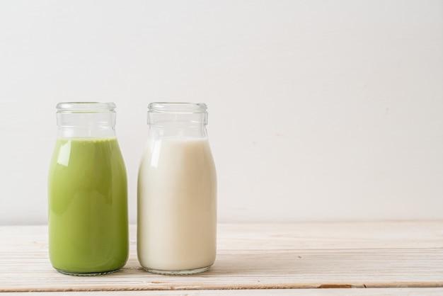 Thé vert matcha latte avec du lait frais en bouteille sur bois
