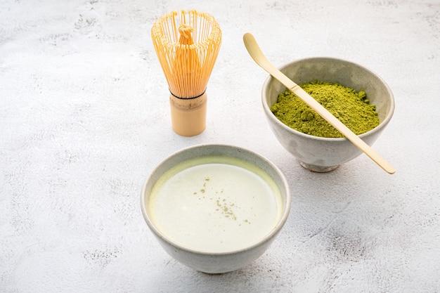Thé vert matcha en poudre avec installation de brosse fouet en bambou matcha sur fond de béton blanc