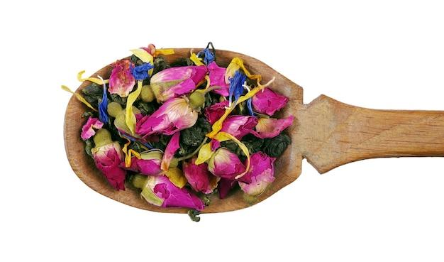 Thé vert mélangé. feuilles de thé vert avec des fleurs de rose séchées dans une cuillère en bois isolée sur blanc.