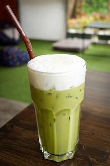 Thé vert à la mousse de lait thé vert glacé en verre avec paille de thé vert ice matcha sur table en c