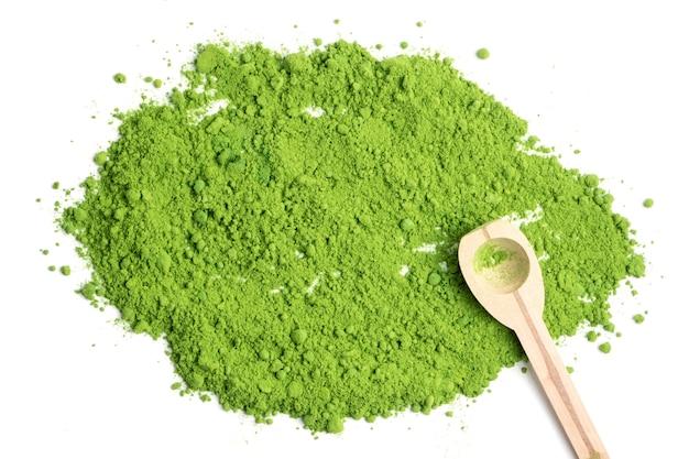 Thé vert en poudre avec cuillère woonden sur fond blanc.