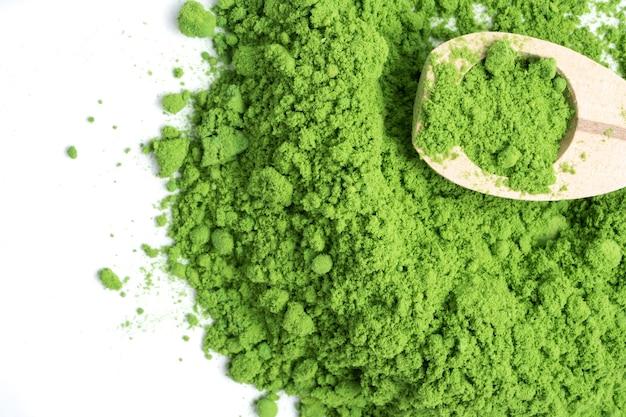 Thé vert en poudre avec une cuillère woonden sur fond blanc.