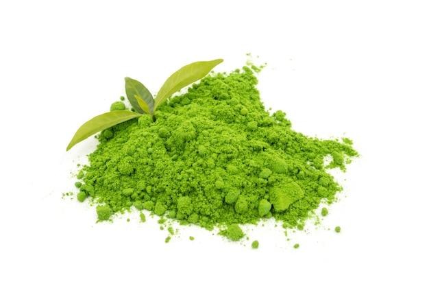 Thé vert en poudre avec des feuilles sur fond blanc.