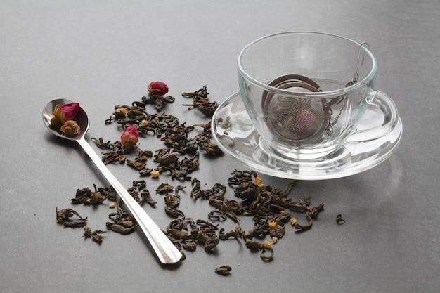 Thé vert renversé avec une rose sur une table en pierre