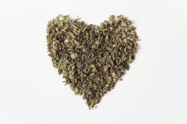 Thé vert sec, forme de coeur. fond blanc. vue de dessus