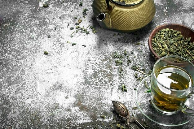 Thé vert avec une théière sur fond rustique