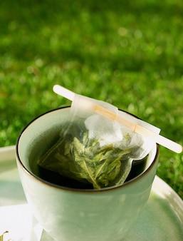 Thé à la verveine au citron dans une tasse avec un sachet de thé fait à la main sur un bureau en herbe sur le balcon. concept de confort. mise au point sélective. fermer. lumière naturelle.