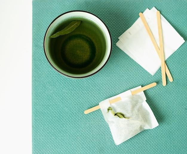 Thé à la verveine au citron dans une tasse avec un sachet de thé fait à la main sur un bureau vert marée. vue de dessus. mise à plat