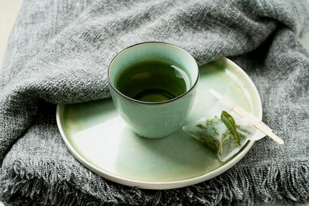 Thé à la verveine au citron dans une tasse avec un sachet de thé fait à la main sur une couverture grise. concept de confort. mise au point sélective. fermer.
