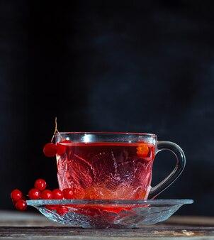 Thé viburnum chaud dans une tasse transparente avec une poignée