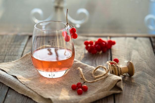 Thé à la viorne chaud dans un verre avec sur une table en bois gris, à côté de baies fraîches de viorne. thé sain de viorne