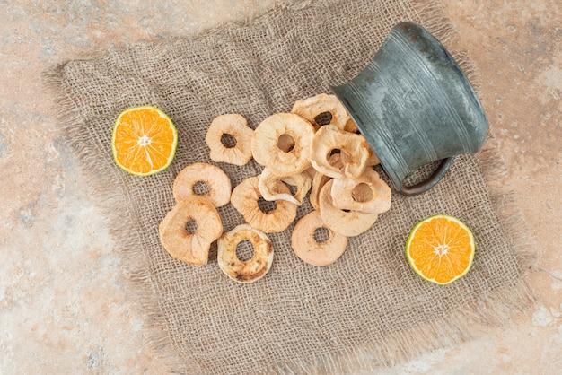 Théière ancienne pleine de pommes séchées avec mandarine coupée à moitié