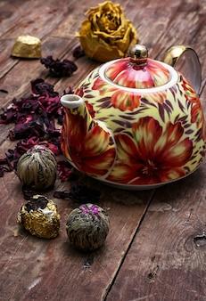 Théière en arrière-plan de sortes d'élite de thé
