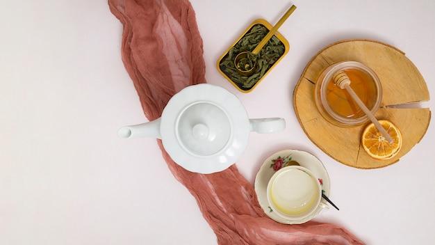 Théière à base de plantes; feuilles; louche de miel; agrumes séchés; tasse en céramique et soucoupe sur fond blanc