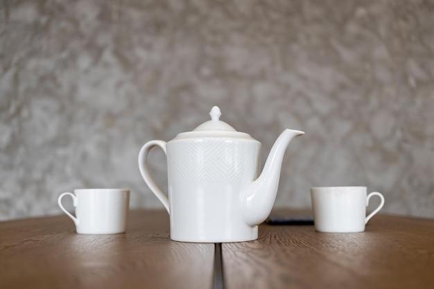 Une théière blanche et deux tasses se tiennent sur une table marron