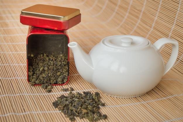 Théière et une boîte de thé vert asiatique traditionnel en vrac