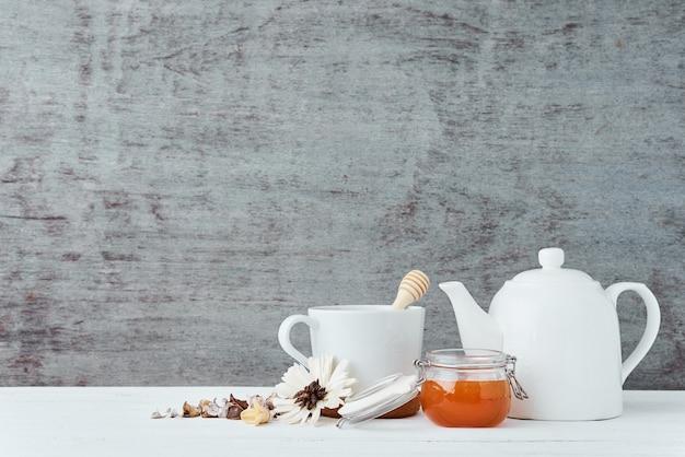 Théière en céramique blanche, tasse et miel en pot de verre sur un bois avec espace de copie