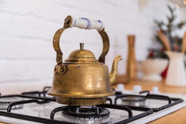 Théière en cuivre vintage sur une cuisinière à gaz.