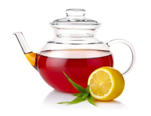 Théière avec du thé noir, des feuilles vertes et des tranches de citron isolés on white