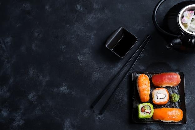 Théière en fer noir et sushi fixés sur une plaque d'ardoise sur une table en pierre noire, poser à plat