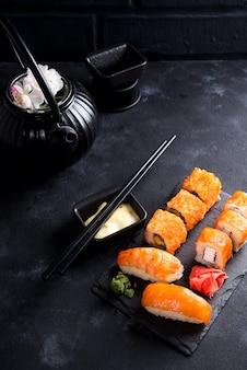 Théière en fer noir et sushi sur une plaque d'ardoise sur une table en pierre noire