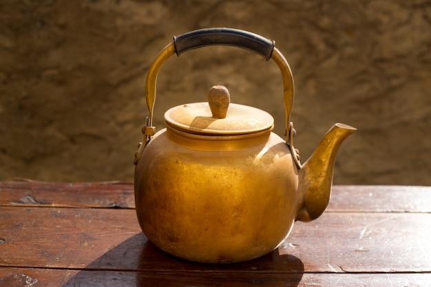Théière en laiton antique sur table en bois vintage