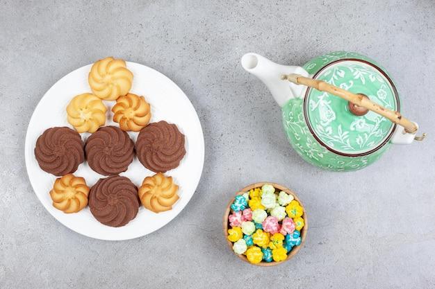 Une théière ornée, un bol de bonbons et une assiette de cookies sur une surface en marbre