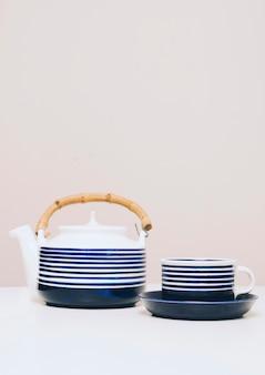 Théière à rayures bleues et tasse sur un bureau blanc sur fond