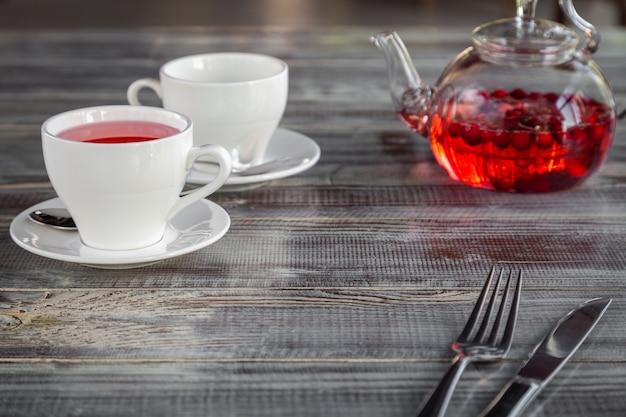 Théière rouge baie rose, tasses blanches, couverts sur fond de bois gris