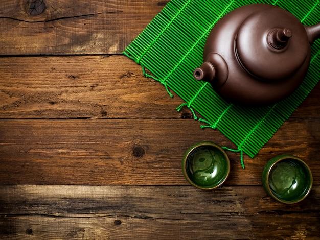 Théière sur tapis de bambou vert. vue de dessus