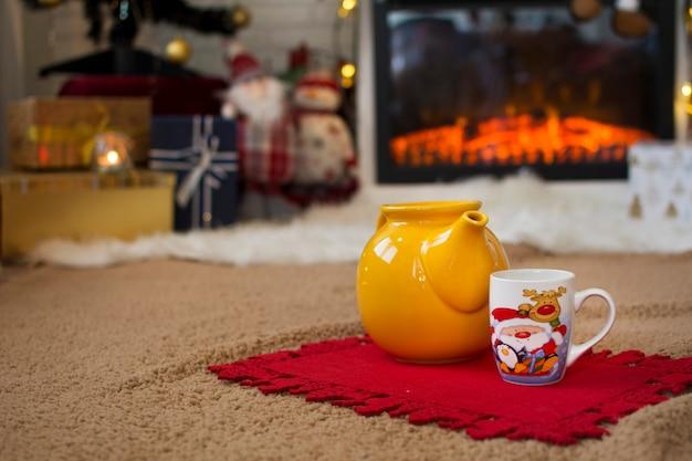 Théière et tasse de noël, sur le tapis à l'intérieur de la maison, avec une atmosphère très douillette et de noël.