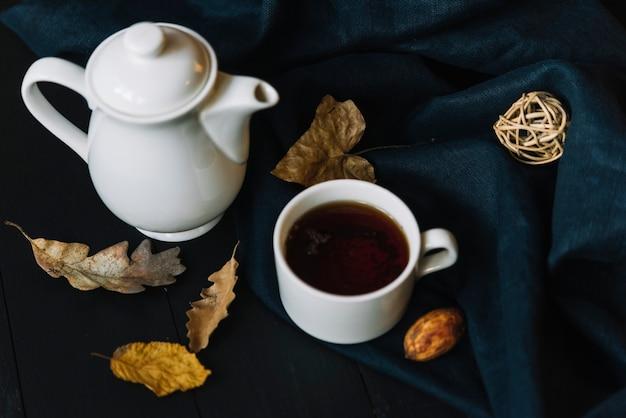 Théière et tasse près des feuilles et des rideaux