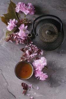 Théière et tasse de thé avec une branche de fleur