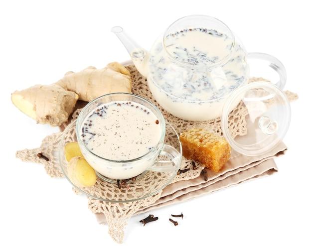 Théière et tasse de thé avec du lait et des épices sur une serviette isolée sur blanc