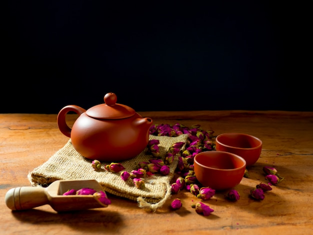 Théière et tasse de thé avec des feuilles de thé rose sur table en bois et fond noir