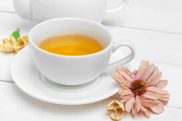 Théière et tasses de thé sur un fond en bois blanc