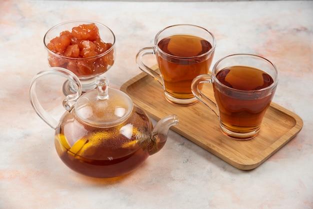 Théière et tasses de thé noir et confiture de coings sur plaque de bois.